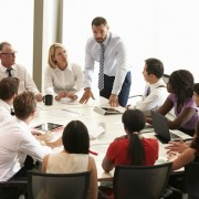 Businessman Addressing Meeting Around Boardroom Table